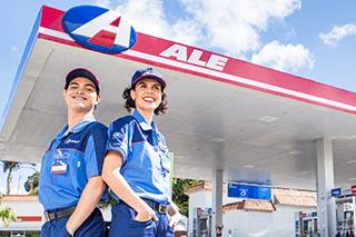 Posto de combustível de bandeira ALE com 2 frentistas sorrindo em frente