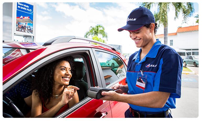 Frentista da ALE, com maquina de cartão na mão, atende, sorrindo, cliente mulher que está em carro vermelho e também sorrindo.