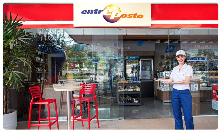 Atendente, sorrindo, com uniforme branco e azul. está em frente a loja de conveniência Entreposto.
