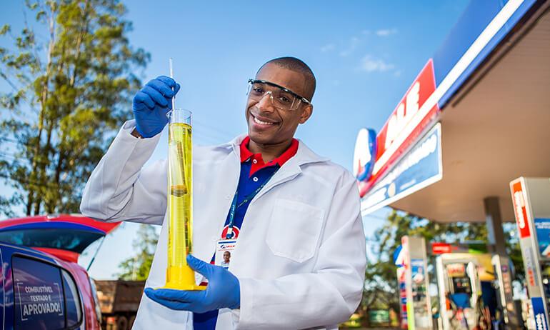 Homem de jaleco branco e óculos de proteção seguro proveta em que ele faz o teste de qualidade do combustível.