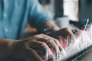 Mão masculina digita em teclado que contém dados holográficos sobre si, o que representa a recuperação do negócio após solicitar um empréstimo ou financiamento.