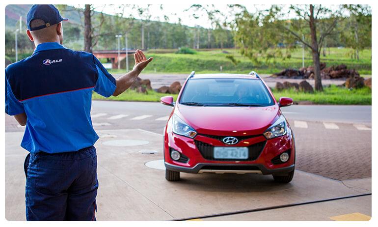 Frentista do Posto ALE ajudando carro a ser manobrado no posto de combustível