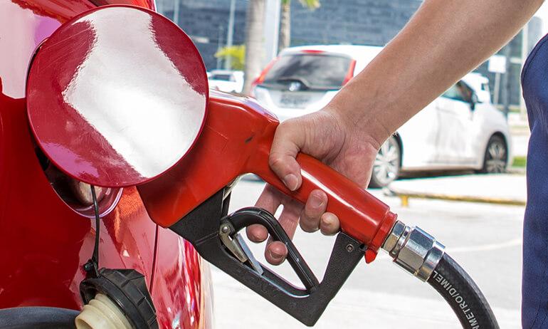 Mão masculina segurando bomba de gasolina vermelha que abastece um carro também vermelho.
