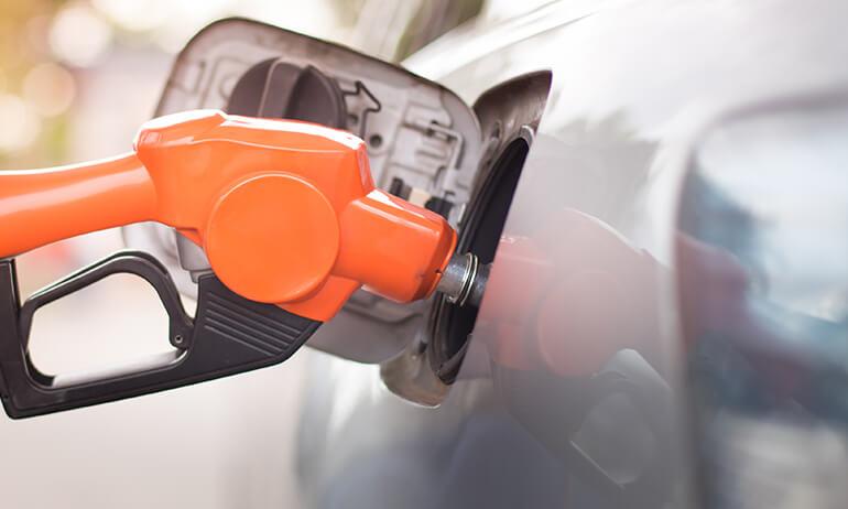Bomba de gasolina laranja abastecendo carro cinza.