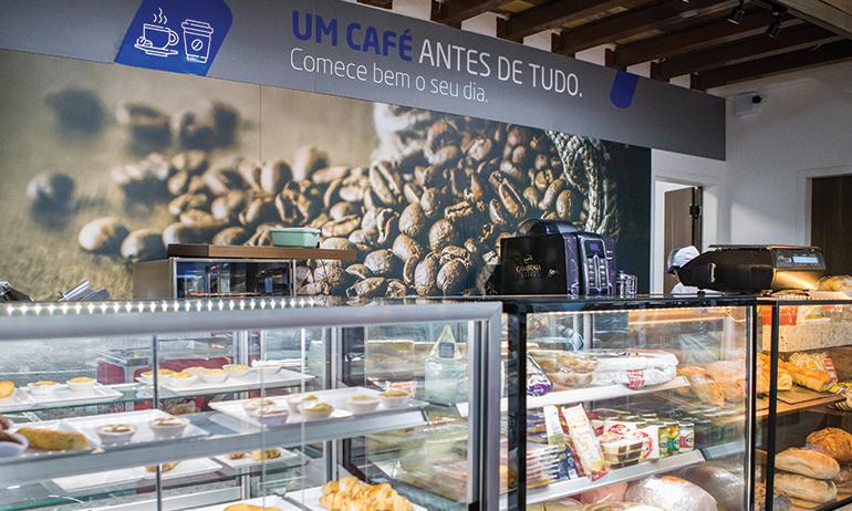 Interior da loja de conveniência Entreposto dos Postos ALE com diversas opções de consumíveis, como café e pães.