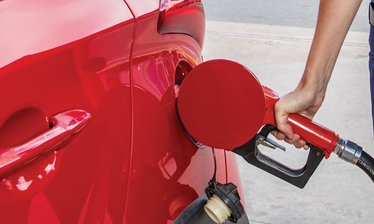 Mão masculina de frentista abastecendo com bomba vermelha, de gasolina, um carro também vermelho.